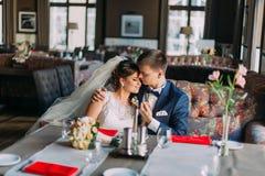O recém-casado enloved os noivos que guardam-se ao sentar-se no sofá Interior brilhante luxuoso com janelas grandes como Fotos de Stock