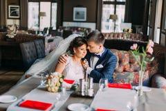 O recém-casado enloved os pares que guardam-se ao sentar-se no sofá Interior brilhante luxuoso com as janelas grandes como o fund Imagens de Stock Royalty Free