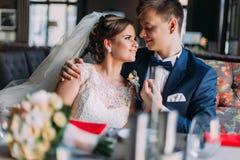 O recém-casado enloved os pares românticos que guardam-se ao sentar-se no sofá Interior brilhante luxuoso com janelas grandes com Fotografia de Stock
