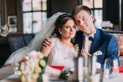 O recém-casado feliz enloved os pares que guardam-se ao sentar-se no sofá Interior brilhante luxuoso com janelas grandes como Imagem de Stock Royalty Free