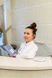 O recepcionista da mulher no revestimento médico está na mesa de recepção Imagens de Stock Royalty Free