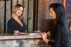 O recepcionista louro bonito da mulher olha com um sorriso em você e mostra um cliente do menu imagem de stock royalty free
