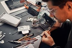 O recruta usa a lente de aumento e a chave de fenda para reparar o smartphone danificado na oficina foto de stock