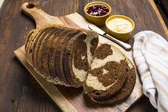 O redemoinho do pão de centeio integral e do centeio pana fatias na placa de corte Foto de Stock