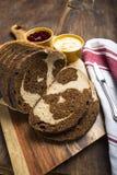 O redemoinho do pão de centeio integral e do centeio pana fatias na placa de corte Imagens de Stock