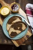 O redemoinho do pão de centeio integral e do centeio pana fatias na placa de corte Fotos de Stock Royalty Free