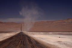 O redemoinho no horizonte da estrada de terra infinita desperdiça completamente o plano estéril no deserto de Atacama, o Chile fotografia de stock