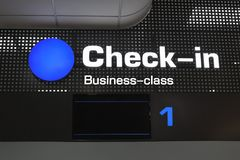 O registro dos passageiros da classe executiva verifica dentro a mesa no aeroporto internacional imagem de stock