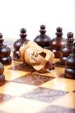 O rei branco da xadrez checkmated pela equipe de oposição, fundo branco, espaço da cópia Fotografia de Stock