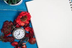 O relógio de bolso dourado do vintage pôs sobre uma tabela de madeira azul com caderno vazio e as flores secadas vermelhas com ar imagem de stock