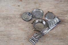 O relógio desmontado encontra-se na tabela de madeira Imagens de Stock Royalty Free