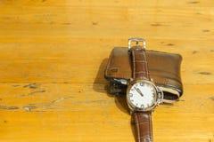 O relógio dos homens e a carteira dos homens de couro marrons com as cédulas na textura de madeira marrom Fotografia de Stock Royalty Free