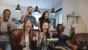 O relógio intercultural do grupo ostenta o jogo na tevê Os suportes apaixonado comemoram o objetivo com bebidas fim do movimento  imagem de stock royalty free