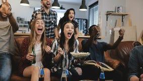 O relógio intercultural do grupo ostenta o jogo na tevê Os suportes apaixonado comemoram o objetivo com bebidas fim do movimento  imagens de stock royalty free