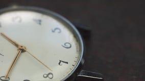 O relógio velho elegante encontra-se na tabela de madeira filme
