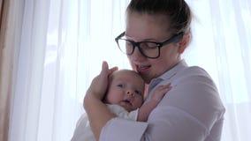 o relacionamento da Mãe-criança, mum novo consola o infante nos braços na sala na luz natural perto da janela vídeos de arquivo