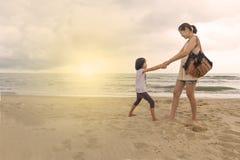 O relacionamento da mãe e da criança joga o mar dianteiro da praia Imagem de Stock