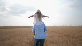 O relacionamento de família, paizinho novo alegre corre com a filha em seus ombros que agita suas mãos na grão dourada filme
