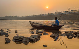 O remador senta-se em seu barco para suportar no por do sol no rio Damodar perto da barragem de Durgapur foto de stock royalty free
