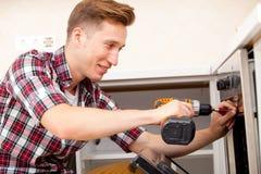 O reparador ajustou o forno na cozinha Fotografia de Stock Royalty Free