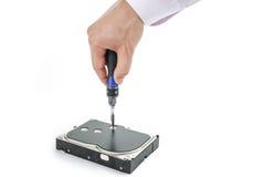 O reparador da mão desaparafusa os 3 tampa do disco rígido de 5 polegadas com uma chave de fenda Foto de Stock Royalty Free