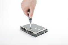 O reparador da mão desaparafusa os 3 tampa do disco rígido de 5 polegadas com uma chave de fenda Fotografia de Stock