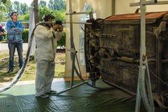 O reparador demonstra o dispositivo para limpar o corpo de carro contra a corrosão fotografia de stock royalty free