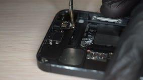 O reparador desmonta o smartphone com chave de fenda video estoque
