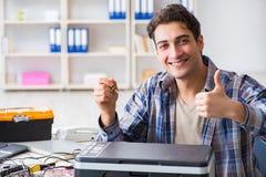O reparador do hardware que repara o fax quebrado da impressora imagens de stock royalty free