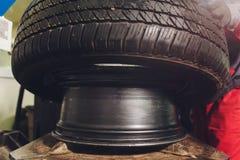 O reparador equilibra a roda e instala o pneu sem c?mara de ar do carro no equilibrador na oficina imagens de stock