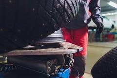 O reparador equilibra a roda e instala o pneu sem c?mara de ar do carro no equilibrador na oficina foto de stock