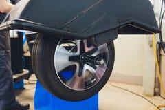 O reparador equilibra a roda e instala o pneu sem c?mara de ar do carro no equilibrador na oficina imagem de stock