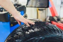 O reparador equilibra a roda e instala o pneu sem c?mara de ar do carro no equilibrador na oficina imagens de stock royalty free