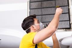 O reparador que repara a unidade de condicionamento de ar do teto foto de stock royalty free