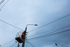 o reparador repara a eletricidade no polo no mau tempo Fotografia de Stock