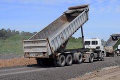 O reparo da estrada, caminhões trouxe a areia, pedras a fim dobrar o asvalt novo foto de stock royalty free