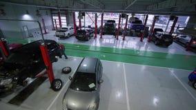 O reparo do carro, carros do lote em elevadores e no assoalho durante a manutenção e os técnicos anda durante o trabalho na grand video estoque