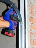 O reparo do contratante e instala a porta da garagem Substitua uma mola quebrada da porta da garagem imagem de stock royalty free