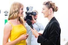 O repórter e o operador cinematográfico disparam em uma entrevista Imagens de Stock