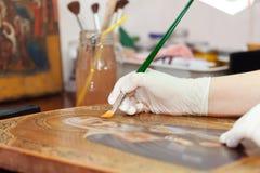 O restaurador da arte funciona no ícone dourado antigo Imagens de Stock Royalty Free