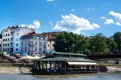 O restaurante de flutuação no rio de Nisava no dia ensolarado e a cidade ajardinam imagem de stock royalty free