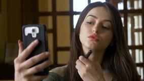 O retoque adolescente bonito compõe com seu telefone esperto usando a escova para aplicar-se cora em seus mordentes video estoque