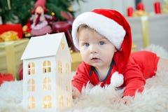 O retrato adorável do bebê pequeno bonito comemora o Natal Feriados do ` s do ano novo Menino em um traje de Santa com a casa do  Fotografia de Stock