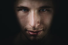 O retrato adulto novo escuro do homem desvanece-se no preto foto de stock