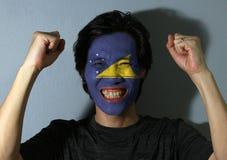 O retrato alegre de um homem com a bandeira de Tokelau pintou em sua cara no fundo cinzento imagem de stock royalty free