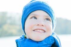 O retrato alegre do close-up do rapaz pequeno com azul fez malha o chapéu fotografia de stock