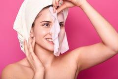 O retrato ascendente próximo da moça bonita com poses despidas dos ombros no fundo cor-de-rosa, remove a máscara facial, conceito foto de stock royalty free