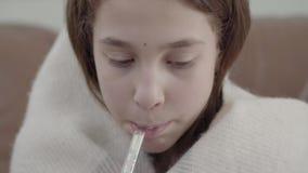 O retrato ascendente próximo do adolescente envolvido em uma cobertura toma um termômetro em sua boca e mede a temperatura video estoque