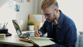 O retrato ascendente próximo do homem atrativo novo com vidros e cabelo amarelo faz anotações no diário Freelancer da casa que wo