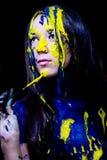 O retrato ascendente próximo da beleza/forma da mulher pintou azul e amarelo com escovas e pintura no fundo preto Imagens de Stock Royalty Free